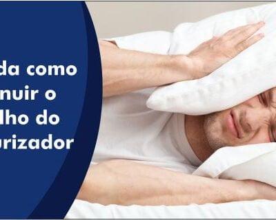 Foto demonstrativa de uma pessoa com um travesseiro na cabeça tentando dormir, mas por causa do ruído do pressurizador não consegue.