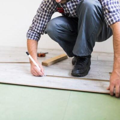 homem de camisa listrada colocando piso vinílico no chão de um cômodo