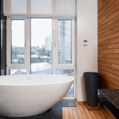 banheiro com piso e parede de madeira , uma banheira branca elevada do chão, pia preta do lado direito da imagem e uma janela na frente da banheira