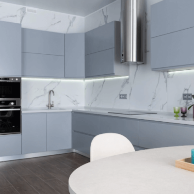cozinha com uma mesa branca com três velas em cima e armários cinza claro e cinza escuro