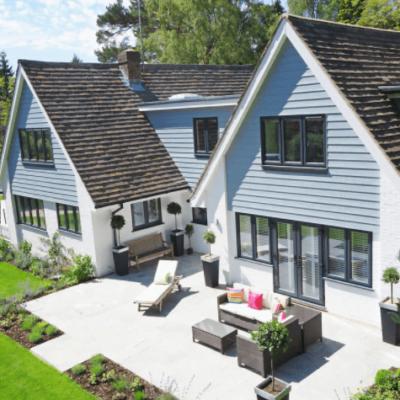 imagem de casa com telhado triangular e área com mesa na frente da casa perto de gramado