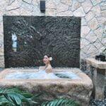 Mulher em uma banheira jacuzzi na área externa. A banheira é de pedras e há vegetação ao redor. capa da manutenção da Jacuzzi